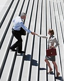 Business people shaking hands on steps outdoors