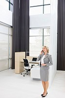 Businesswoman talking on cell phone in office (thumbnail)