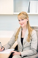 Smiling businesswoman writing on notepad at desk