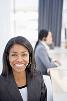 Smiling businesswoman wearing headset in office