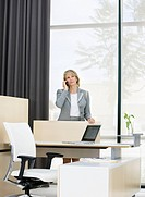 Businesswoman talking on cell phone at desk in office