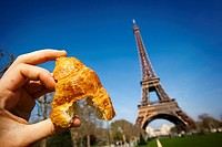 hand holding a croissant in Eiffel Tower, Paris