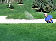 Golfer hitting ball out of sand trap, ball in air heading toward green