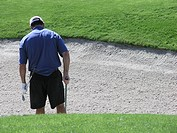 Golfer raking sand trap after hitting ball out, rear view