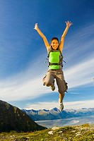 Young adult Hispanic woman leaps with joy while on top of Mt. Alyeska with view of Chugach Mountains near Girdwood in Southcentral Alaska