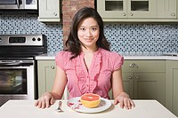 Young woman eating grapefruit