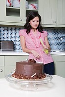Young woman eating celery, watching chocolate cake