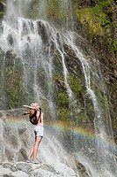Woman standing by waterfall with arms open (thumbnail)