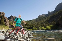 Man with mountain bike by lake