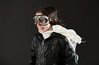 Young boy wearing flying goggles, dressed as pilot