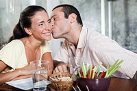 Man kissing woman on cheek at table