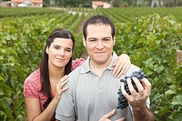 Couple in a vineyard with grapes