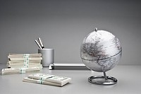 Silver globe with stacks of US currency