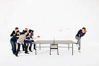 Group playing table tennis against one man