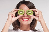 Woman holding two kiwi halves over her eyes