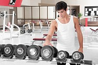 Man choosing dumbbells in a gym