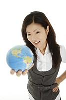 Beautiful Asian businesswoman with the world in the palm of her hand