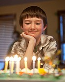 Boy, age 10, looks at his birthday cake during party.