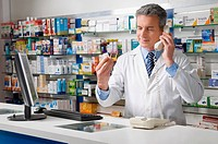 Pharmacist looking at a drug bottle and talking on the telephone