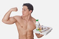 Man holding food supplements and flexing biceps