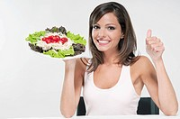 Woman making a thumbs up sign with a plate of salad