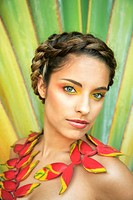Hawaii, Oahu, Headshot of Attractive Beautiful Female with braided hair and heliconia flowers around her neck.