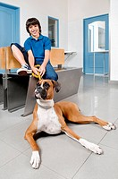 Boy sitting with a dog in a veterinary hospital