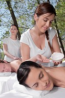 Couple receiving back massage from massage therapists