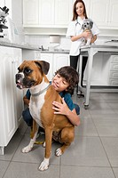 Boy hugging a dog with a vet in the background