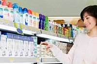 Woman buying cosmetics in a supermarket