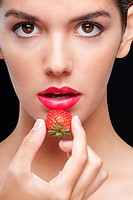 Portrait of a woman holding a strawberry