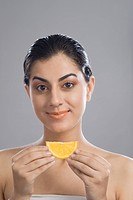 Portrait of a woman holding a slice of orange
