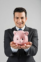 Portrait of a businessman holding a piggy bank
