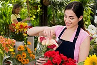 Woman holding a bouquet of flowers and smiling in a greenhouse