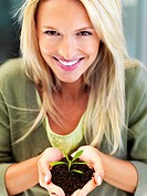 Happy woman holding a young plant
