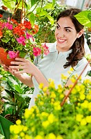 Woman holding a hanging basket in a greenhouse