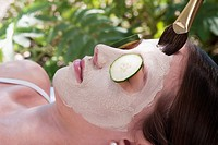 Woman applying a facial mask