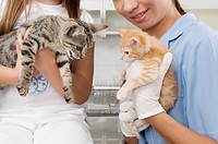 Female vet with a girl carrying cats