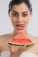 Woman holding a slice of watermelon and licking lips