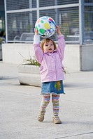 Playful female toddler with a ball