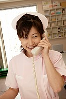 Female nurse using phone at nurses station, smiling