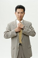 Portrait of businessman adjusting tie, white background