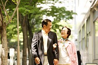 Senior couple walking arm in arm, smiling