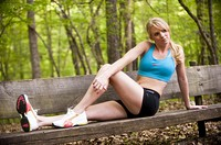 Young blond woman looking away from camera  in work out clothing sitting on a wooden bench in a park setting