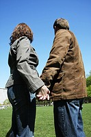 Couple holding hands and looking away on a sunny day in a park