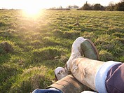 Bright sun and two people in wellingtons sitting in rural field