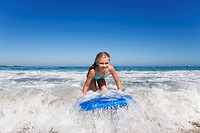 Smiling girl surfing on body board in ocean