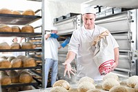 Baker sprinkling loaves of bread with flour