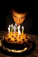 A  picture of a ten year old boy blowing out the candles on his birthday cake in the Uk