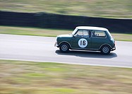 England, West Sussex, Goodwood Revival. Green Mini Cooper on race track at Goodwood Revival.